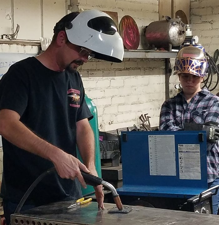 Welding instructor with young student